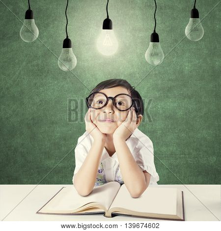 Cute elementary school student with a book on desk looking up at the bright light bulb