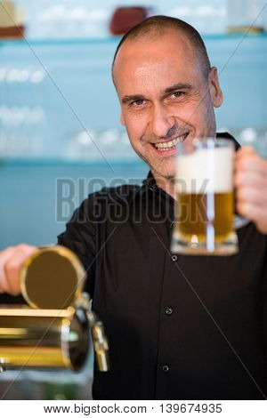 Portrait of bar tender holding beer glass at bar counter