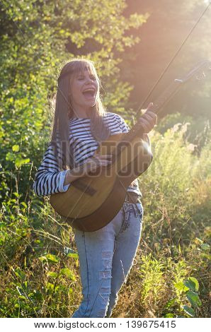 Blond hippie-style girl posing with an acoustic guitar