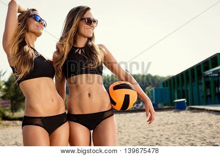 healthy young woman laughing with beachball while on the beach in summer