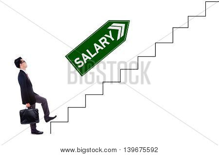 Photo of a young businessman walking upwards on the stairs with salary text on the signpost