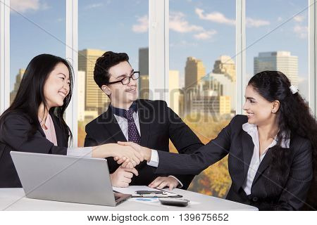 Image of chinese businesswoman shaking hands with indian businesswoman in front of middle eastern businessman shot in the office