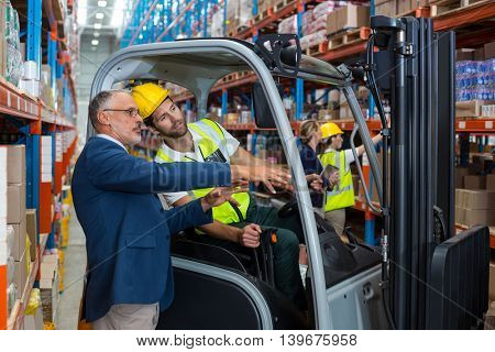 Worker driving forklift discussing with businessman in warehouse