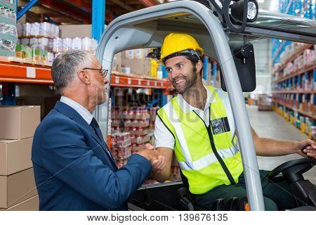 Worker handshaking with well dressed senior person in warehouse