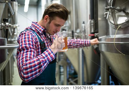 Brewer smelling beer at brewery factory
