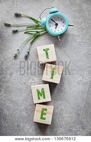 Word TIME with clock on a color background