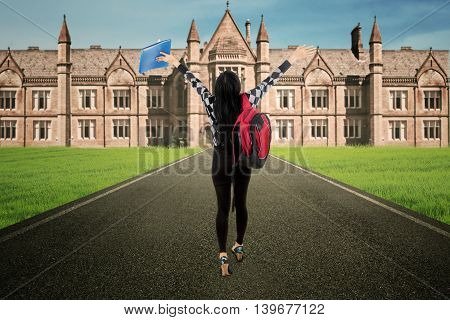 Female student walk alone to campus rear view