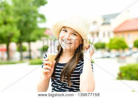 Cute happy girl is eating ice-cream, outdoors