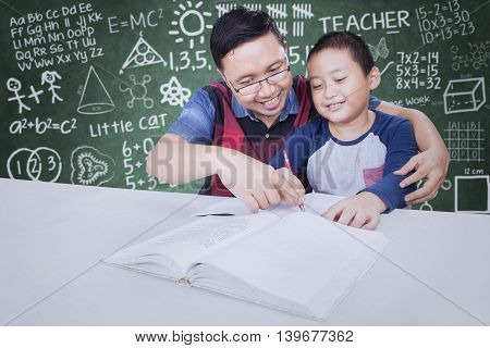 Portrait of male teacher guide a little boy to learn and write on the book shot with doodles background on chalkboard