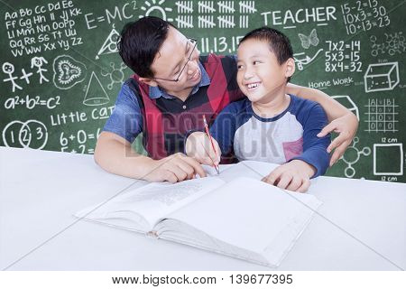 Portrait of male teacher helps a little child to learn shot with doodles background on chalkboard