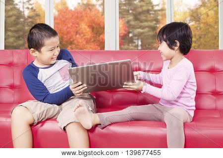 Portrait of two cute children fighting on the sofa to take laptop computer shot at home with autumn background on the window