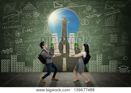 Picture of two high school students carrying a pile of book in front of a door shaped key hole with doodles and upward arrow