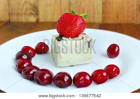 strawberry and cherries on the white plate and cake. Fresh strawberry and cherry on the plate.