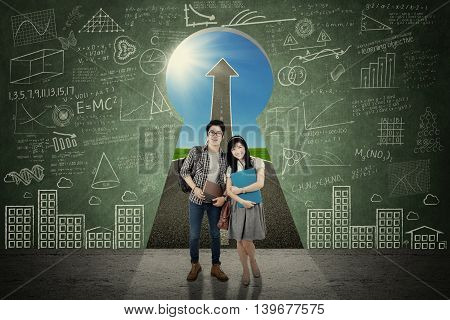 Image of two college students smiling at the camera in front of a door shaped a keyhole with upward arrow and doodles