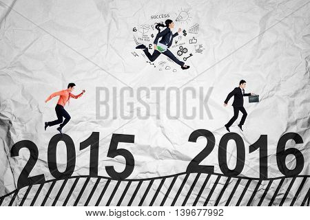 Three entrepreneurs jumping and running above numbers 2015 to 2016 while compete to get success