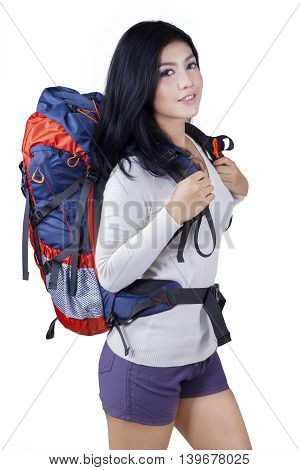 Photo of a young female hiker standing in the studio while carrying bag and smiling at the camera