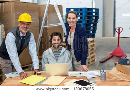 Smiling coworkers looking at camera in warehouse
