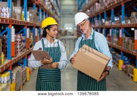 Coworkers examining box in warehouse
