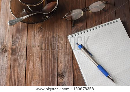 Notepad with pen and glasses do not lie wooden table and next to a cup of coffee.