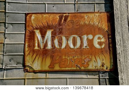 MEDINA, NORTH DAKOTA, July 1, 2016: The old sign  advertises Benjamin Moore paint, a company founded in 1883, is based in Montvale, New Jersey and is presently owned by Berkshire Hathaway.