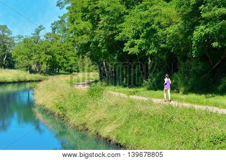 Active woman runner jogging near canal river, outdoors running, sport and healthy lifestyle concept