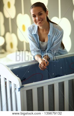 Young woman standing near children's cot.