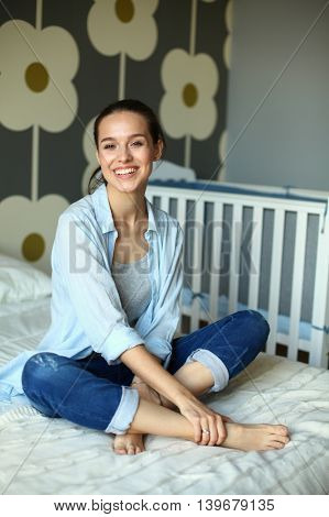 Young woman sitting on the bed near children's cot.
