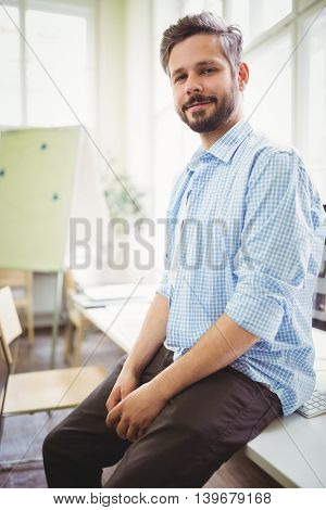 Portrait of smiling businessman sitting on desk in creative office