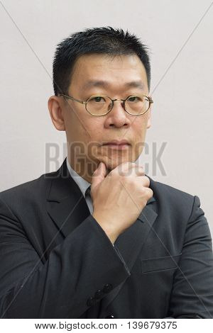 A portrait of an asian man with his hand on his chin
