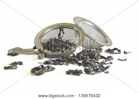 sieve for tea and tea on a white background