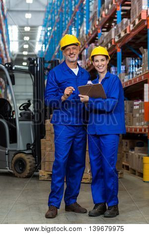 Coworkers looking at camera in warehouse