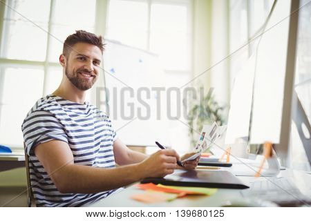 Smiling businessman working at desk in creative office