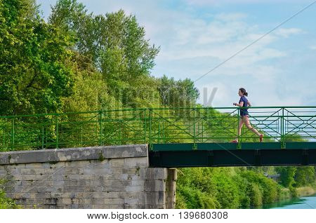 Active woman runner jogging across river bridge, outdoors running, sport and healthy lifestyle concept