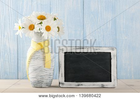 Chamomile flowers in the jug and chalkboard