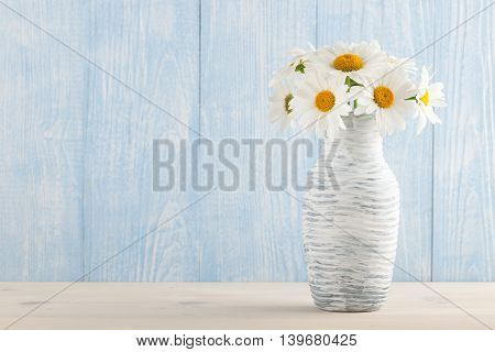 Camomile flowers in the jug on the table