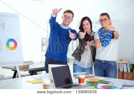 Young business people standing at office near desk and showing ok