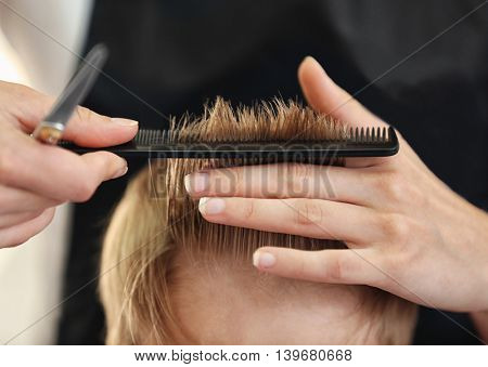 Hairdresser's hands making hairstyle to little boy, close up