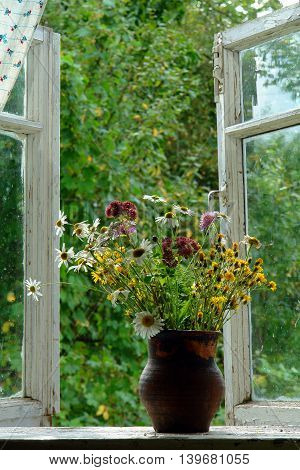 bouquet of wild flowers in a jug on the open window into the garden