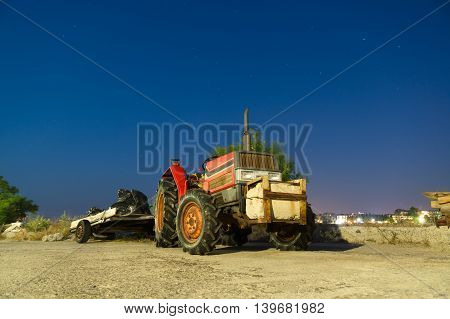 small tractor with a trailer is under the night sky