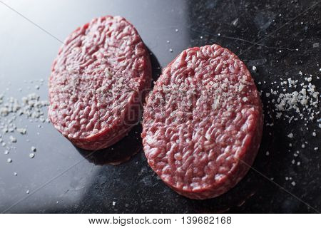 Meat for burgers grilling barbecue bbq. Fresh spicy uncooked delicious beef for hamburgers on dark background with copy space closeup