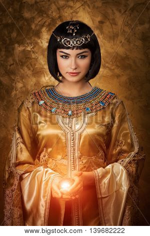 Photo of gorgeous woman with Cleopatra makeup holding magic lighting ball