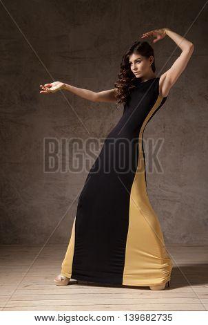 Portrait of young brunette model in long black and beige dress posing in studio