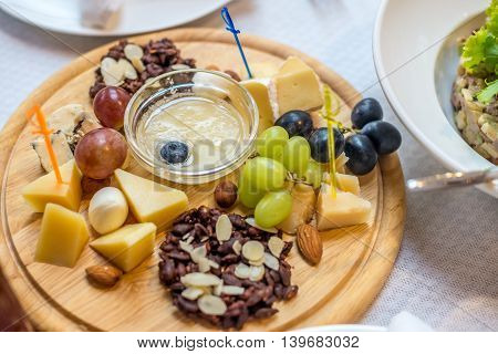 Cheese plate with variety of appetizers on table