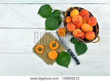 Delicious ripe apricots in a wooden basket with leaves on a light wooden background. Top view. Rustic style. Summer background with fruit. Knife and half sweet apricots on a rough cloth.