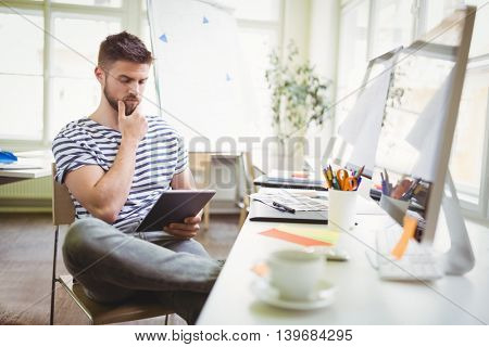 Thoughtful businessman holding digital tablet while sitting in office