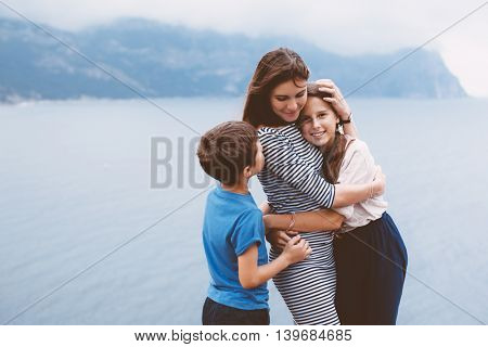 Mom with two preteen children walking outdoor, cool autumn weather