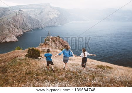Mom with two preteen children walking outdoor, cool weather, beautiful landscape