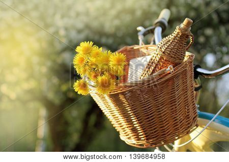 basket with dandelions and wicker bottle for a picnic in the nature