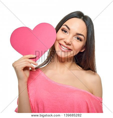 Young happy woman hold Love symbol pink heart, isolated on studio background. Girl with valentine's sign.