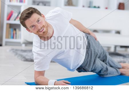 yoga man idoing fitness on a blue mat